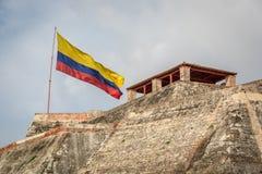 Cartagena, Colombia - la bandera colombiana en el fuerte de Cartagena en un día nublado y ventoso Cartagena, Colombia Imagen de archivo