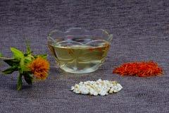 Cartamo per i cosmetici e le spezie ad alimento r Olio vegetale cosmetico in un vetro fotografia stock libera da diritti
