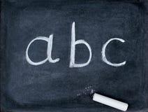 Cartas del ABC y materia de la escuela en la pizarra Imagen de archivo