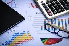 Cartas e gráficos de negócio com nota do vidro e de livro do olho Foto de Stock Royalty Free