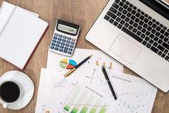 Cartas e gráficos de negócio com portátil Fotografia de Stock Royalty Free