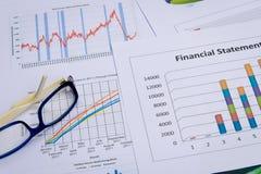 Cartas e gráficos de negócio com vidro do olho Fotografia de Stock Royalty Free