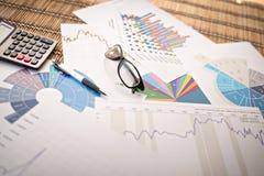 Cartas e gráficos de papel financeiros na tabela Negócios Fotos de Stock Royalty Free