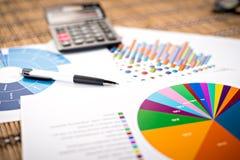 Cartas e gráficos de papel financeiros na tabela Negócios Fotos de Stock