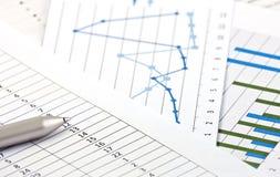 Cartas e gráficos financeiros na tabela Foto de Stock