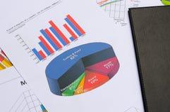 Cartas y gráficos de negocio con el libro Imágenes de archivo libres de regalías