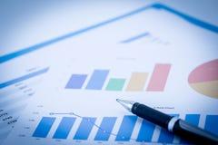 cartas y gráficos de negocio financieros en la tabla Fotos de archivo