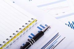 Cartas y gráficos financieros en la tabla del negocio Imagen de archivo libre de regalías