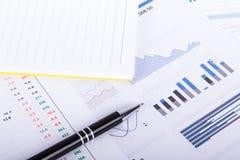 Cartas y gráficos financieros en la tabla del negocio Foto de archivo