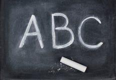Cartas y tiza del ABC en la pizarra Fotografía de archivo
