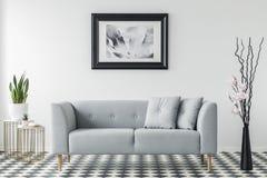 Cartaz acima do sofá cinzento com os descansos no interior mínimo da sala de visitas com a planta na tabela do ouro Foto real fotografia de stock