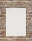 Cartaz de suspensão branco vazio com pregador de roupa e corda na parede de tijolo, fundo Foto de Stock Royalty Free