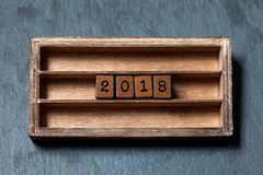 cartaz do convite do cartão de 2018 anos Caixa do vintage, cubos de madeira com letras do estilo antigo Pedra cinzenta textured Fotografia de Stock