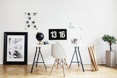 Cartaz e planta no interior branco do espaço de trabalho com a cadeira na mesa com computador de secretária Foto real fotografia de stock