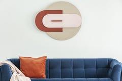 Cartaz moderno na parede branca acima do sofá azul com coxim alaranjado e da cobertura cor-de-rosa no interior Foto real fotografia de stock