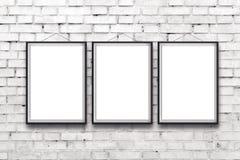 Cartaz vertical vazio de três pinturas no quadro preto fotografia de stock