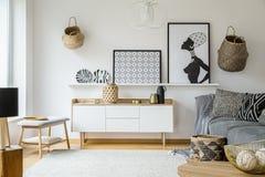 Cartazes e placas acima do armário de madeira na sala de visitas int do boho imagem de stock royalty free