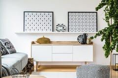 Cartazes modelados acima do armário no interior moderno da sala de visitas Foto de Stock Royalty Free