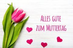 Carte allemande de jour du ` s de mère avec la tulipe et les coeurs de jour du ` s de mère de Muttertag de mot Photographie stock libre de droits