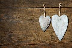 Carte avec deux coeurs en bois sur le fond en bois âgé Images stock
