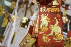 Carte avec l'image d'un singe accrochant sur un arbre de Noël TET venant bientôt An neuf chinois Photos stock