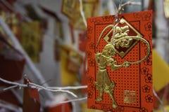 Carte avec l'image d'un singe accrochant sur un arbre de Noël TET venant bientôt An neuf chinois Image libre de droits