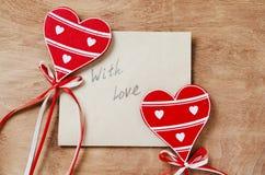 Carte avec le message avec amour à la lettre et aux coeurs rouges en bois Images libres de droits