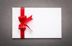 Carte avec les arcs rouges de rubans Photographie stock libre de droits