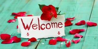 Carte bienvenue d'endroit de rouge et de blanc avec la fleur et les pétales de rose rouges sur la table en bois rustique verte an Photographie stock