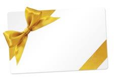Carte cadeaux avec l'arc d'or de ruban d'isolement sur le blanc Image stock