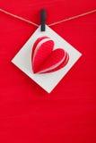 Carte cadeaux blanche avec les coeurs de papier sur le fond en bois rouge Photo stock