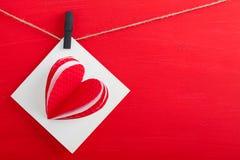 Carte cadeaux blanche avec les coeurs de papier sur le fond en bois rouge Photographie stock libre de droits