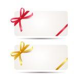 Carte cadeaux con la cinta roja y de oro y un arco en el fondo blanco Plantilla del vale para la invitación del diseño y crédito  Fotos de archivo