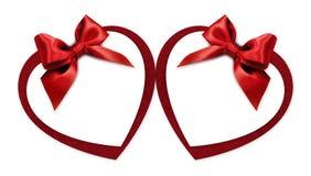Carte cadeaux de la forma del corazón de la tarjeta del día de San Valentín con el arco rojo de la cinta aislado encendido foto de archivo