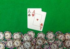 Carte che mostrano le paia degli assi con i chip su verde Immagine Stock Libera da Diritti