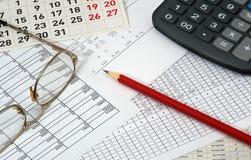 Carte con le figure, il calendario, i vetri, la matita ed il calcolatore Immagini Stock