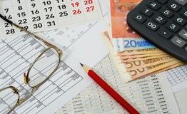 Carte con le figure, il calendario, i vetri, la matita, gli euro ed il Ca Immagine Stock