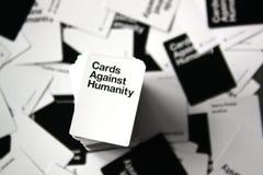 Carte contro la vista sopraelevata di umanità con le carte sparse nel fondo fotografia stock