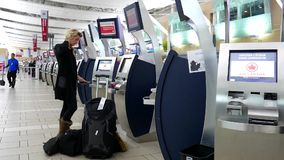 Carte d'embarquement imprimante de femme à la machine d'Air Canada banque de vidéos