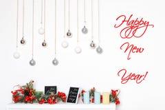 Carte d'an neuf heureux Décorations de vacances d'hiver avec les baies, les bougies et les boules rouges givrées d'argent sur la  image stock