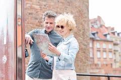 Carte d'une cinquantaine d'années de sourire de lecture de couples dans la ville Photographie stock libre de droits
