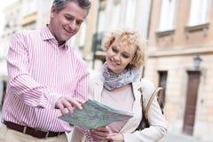 Carte d'une cinquantaine d'années de sourire de lecture de couples dans la ville Photo stock
