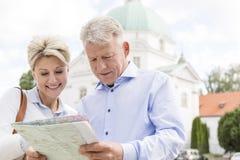 Carte d'une cinquantaine d'années de sourire de lecture de couples dehors Image libre de droits