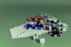Carte da gioco e dadi colorati dei chip su un flash verde del fondo reale fotografie stock