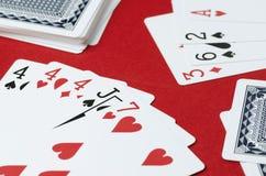 Carte da gioco su un fondo rosso, combinazione in poker, tre di un genere immagine stock
