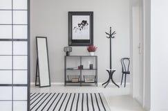 Carte dans le cadre noir sur le mur gris du couloir avec le miroir, l'étagère, le cintre et les cheveux photo libre de droits