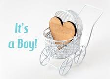 Carte de bébé - sa un thème de garçon Landau avec le coeur en bois sur le fond blanc Carte de voeux nouveau-née Photos libres de droits