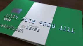 Carte de banque en plastique comportant le drapeau du Nigéria Rendu 3D relié au système d'opérations bancaires nationales Photographie stock