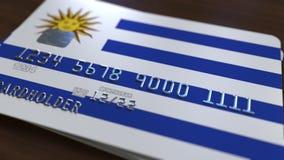 Carte de banque en plastique comportant le drapeau de l'Uruguay Rendu 3D relié au système d'opérations bancaires nationales Photo stock