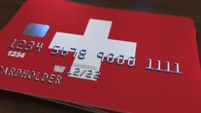 Carte de banque en plastique comportant le drapeau de la Suisse Rendu 3D relié au système d'opérations bancaires nationales Photographie stock